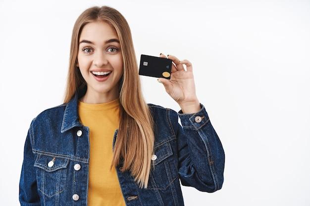 Mädchen mag bargeldlos bezahlen, kreditkarte für online-käufe verwenden, leicht reisen, bankkarte halten und breit lächeln, um den firmenservice zu empfehlen, neue funktionen erklären