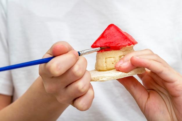 Mädchen malt das haus aus ton oder salzigem teig mit acrylfarben