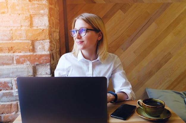 Mädchen-manager, freiberufler, geschäftsdame, die an einem laptop in einem café arbeitet oder zusammenarbeitet.