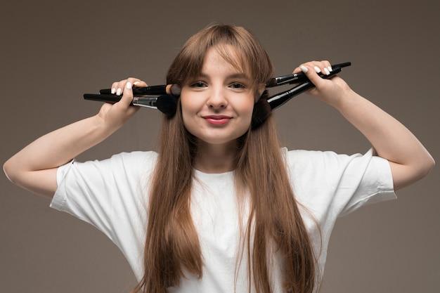 Mädchen maskenbildner mit make-up pinsel breitete ihre arme an den seiten an einer dunklen wand aus