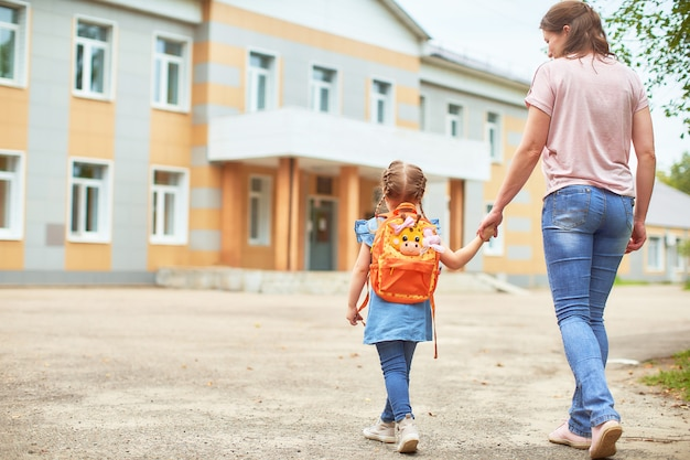 Mädchen mit aktentaschen in der nähe der schule.