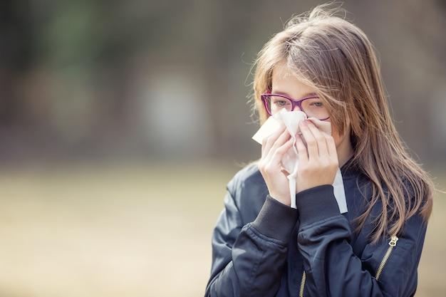 Mädchen mit allergiesymptom, das nase weht. jugendlich mädchen mit einem taschentuch in einem park.