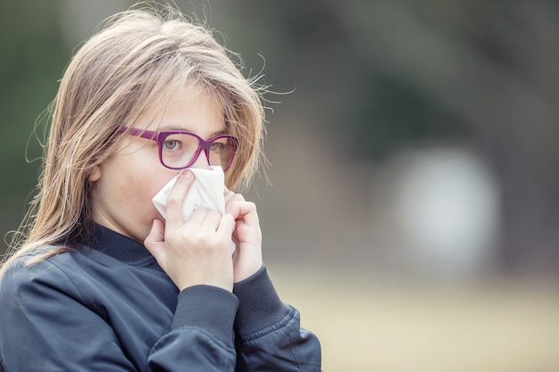 Mädchen mit allergiesymptom, das nase weht. jugendlich mädchen mit einem taschentuch in einem park. Premium Fotos
