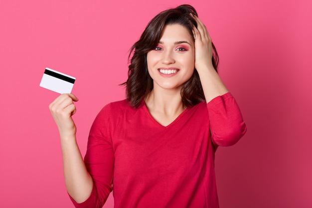 Mädchen mit angenehmem aussehen hält kreditkarte in ihren händen, gewinnt geld in der lotterie, frau im roten outfit sieht glücklich aus, zahlt für einkäufe mit karte, hält handfläche auf herde.
