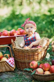 Mädchen mit apfel im apfelgarten. schönes mädchen, das organisches apple im obstgarten isst.
