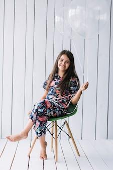 Mädchen mit ballonen auf stuhl