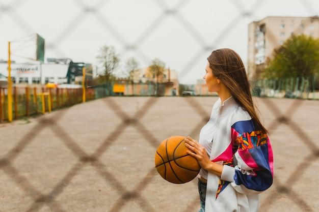 Mädchen mit basketball hinter zaun