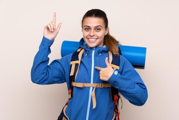 Mädchen mit bergsteigerrucksack über lokalisierter wand