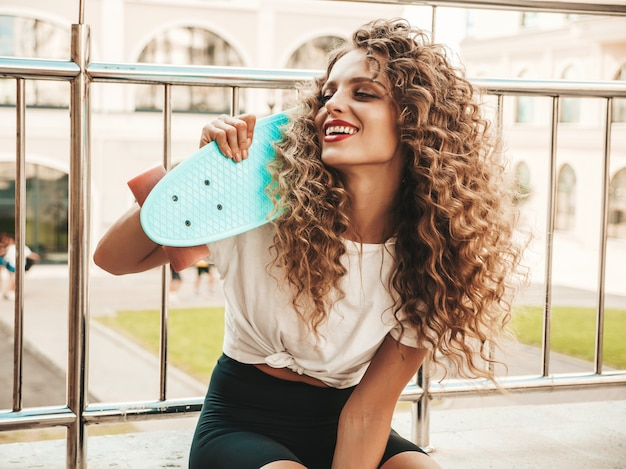 Mädchen mit blauem penny-skateboard, das auf der straße aufwirft