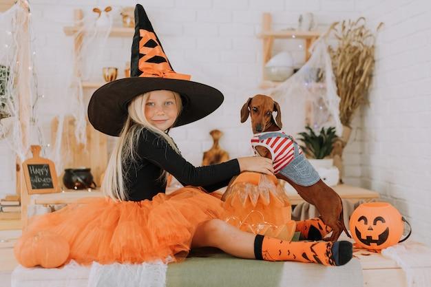Mädchen mit blauen augen in einem halloween-hexenkostüm und einem winzigen dackel in einem hundeoverall