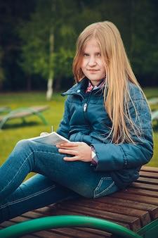 Mädchen mit blondem haar, das einen brief auf einer hölzernen chaiselongue im frühjahr schreibt
