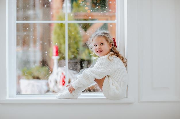 Mädchen mit blondem lockigem haar und rotem weihnachtsbogen nahe dem großen fenster