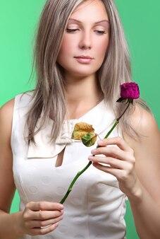 Mädchen mit blume. traurige schöne frau, die getrocknete rote rose hält