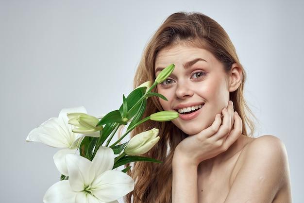 Mädchen mit blumen beschnitten ansicht porträt nahaufnahme frühling nackte schultern klare haut make up