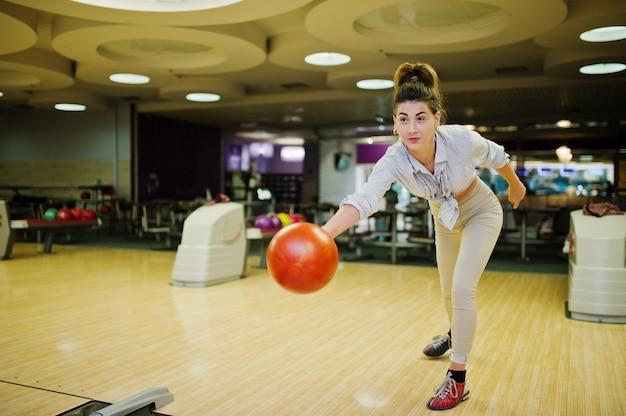 Mädchen mit bowlingkugel auf der gasse spielte am bowlingspielverein.