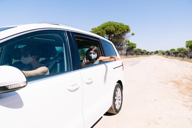 Mädchen mit braunen haaren mit gesichtsmaske und sonnenbrille, die aus dem autofenster späht und in den urlaub eine kiefernstraße hinunter mitten in der covid19 coronavirus-pandemie fährt