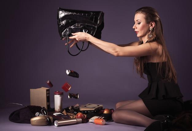 Mädchen mit braunen haaren und im schwarzen kleid sitzt und schüttelt dinge aus der tasche auf dem boden