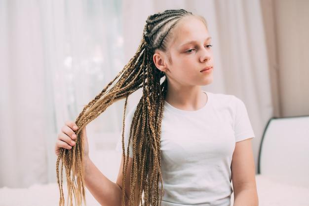 Mädchen mit braunen haaren und zöpfen mit künstlichem haar geflochten
