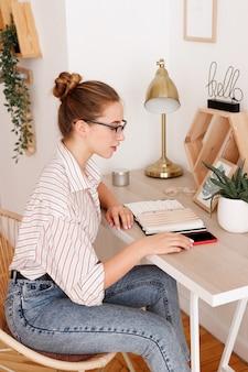 Mädchen mit brille arbeitet zu hause mit telefon aus der ferne