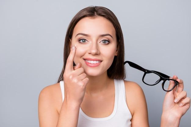 Mädchen mit brille in der hand lokalisiert auf grau
