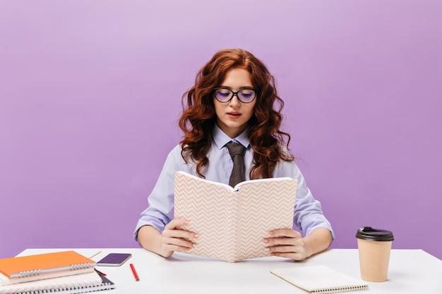 Mädchen mit brille liest buch an lila wand