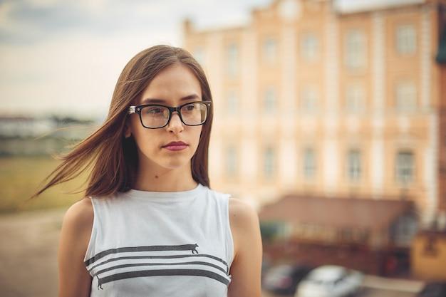 Mädchen mit brille. stadtporträt im sommer auf dem hintergrund von gebäuden.