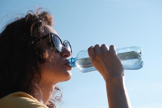 Mädchen mit brille trinkt bei heißem wetter wasser aus einer flasche.