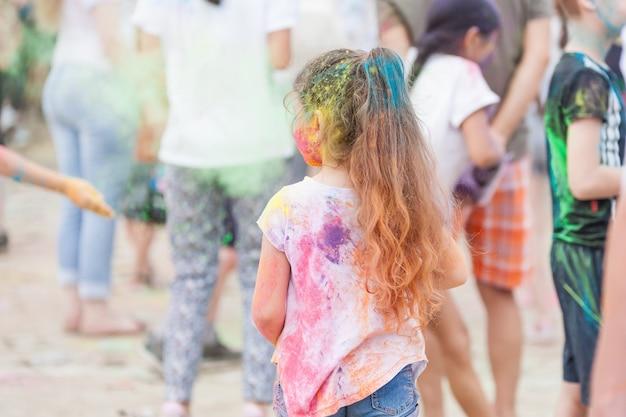 Mädchen mit buntem rücken und haaren auf holi festival