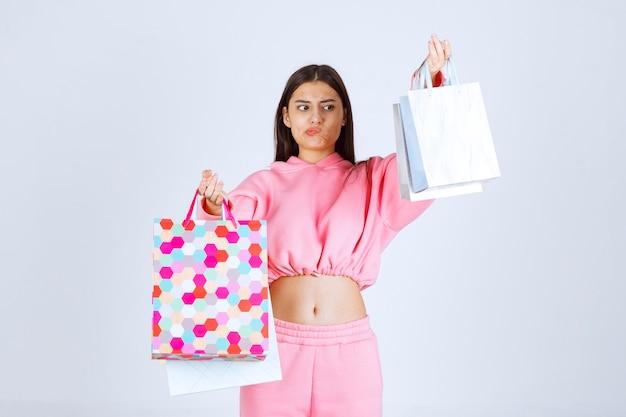 Mädchen mit bunten einkaufstaschen sieht unzufrieden aus.