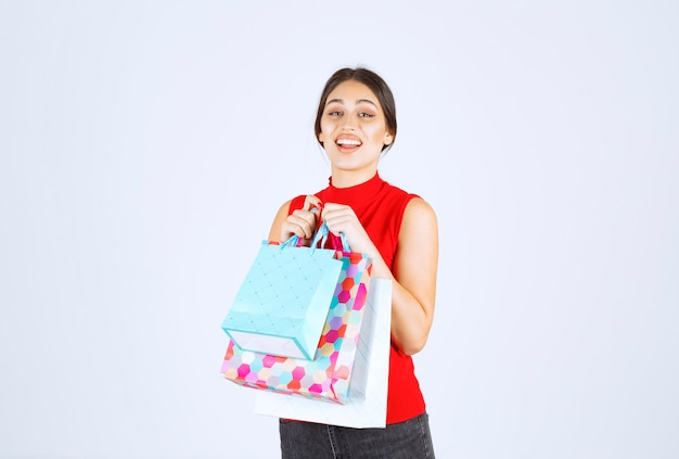 Mädchen mit bunten einkaufstüten, die sich positiv fühlen.