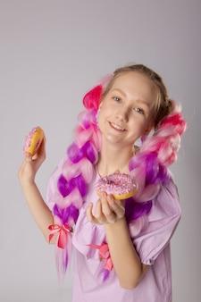 Mädchen mit bunten zöpfen und donuts