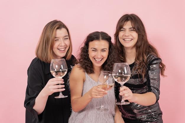 Mädchen mit champagner haben spaß auf rosafarbenem hintergrund, party, feier.