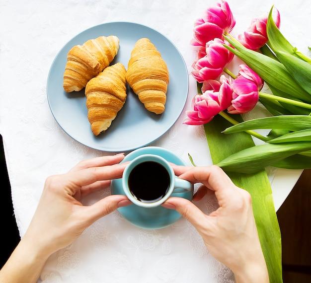 Mädchen mit croissants und kaffee, ein strauß rosa tulpen, glücklicher morgen