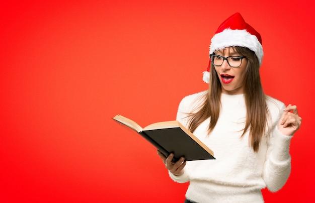 Mädchen mit dem feiern der weihnachtsfeiertage, die ein buch halten und überrascht