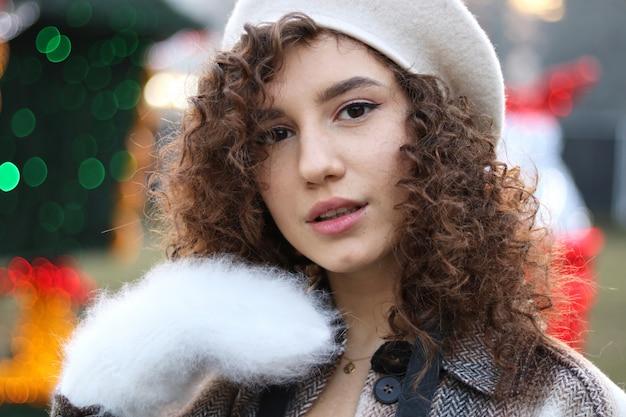 Mädchen mit dem gelockten haar, das weiße handschuhe am weihnachtsmarkt hält