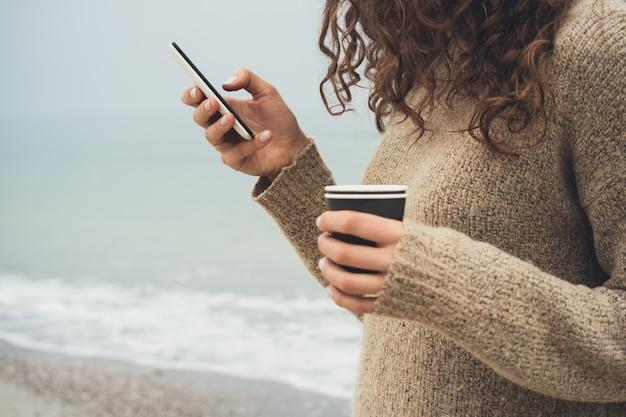 Mädchen mit dem gelockten haar in einer braunen strickjacke geht auf den strand, unter verwendung des handys und des trinkenden kaffees