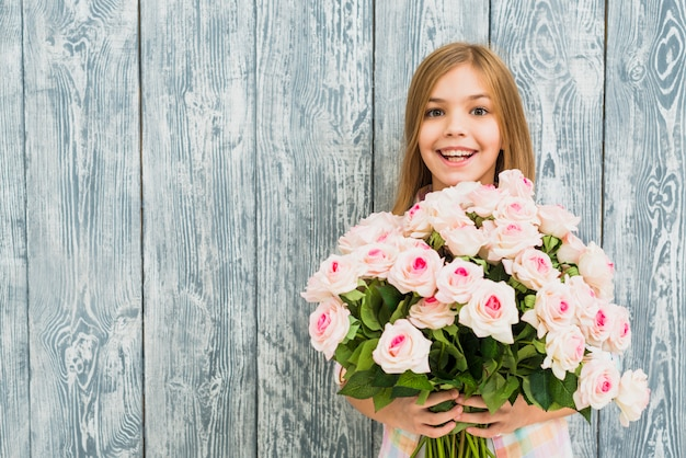Mädchen mit dem glücklichen überraschten gesicht, das rosen hält