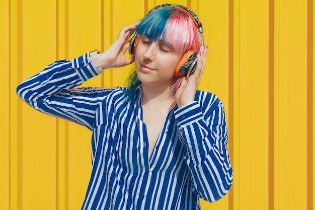 Mädchen mit dem haar färbte das hören musik mit kopfhörern