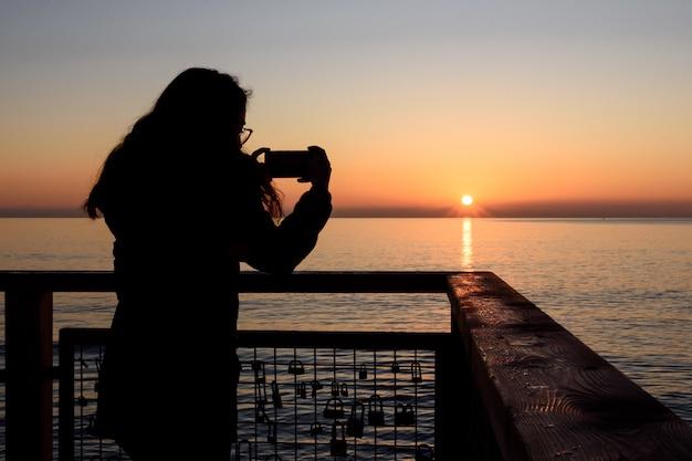 Mädchen mit dem handy sonnenaufgang am strand fotografieren