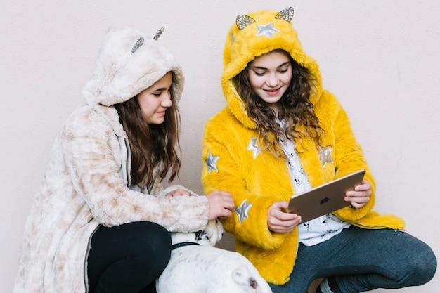 Mädchen mit dem hund, der tablette betrachtet