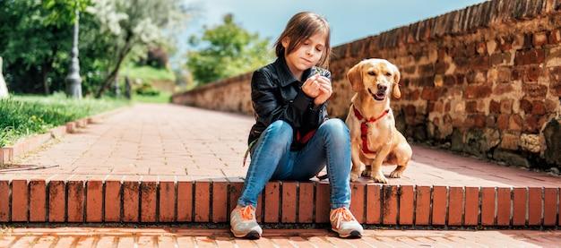 Mädchen mit dem hund sitzt auf der treppe