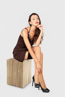 Mädchen mit dem langen gelockten haar, das im kurzen kleid und in den strümpfen mit strumpfband sitzt