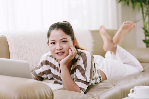 Mädchen mit dem laptop, der auf sofa stillsteht