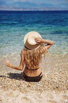 Mädchen mit dem lockigen blonden haar im schwarzen bikini, der am strand entspannt