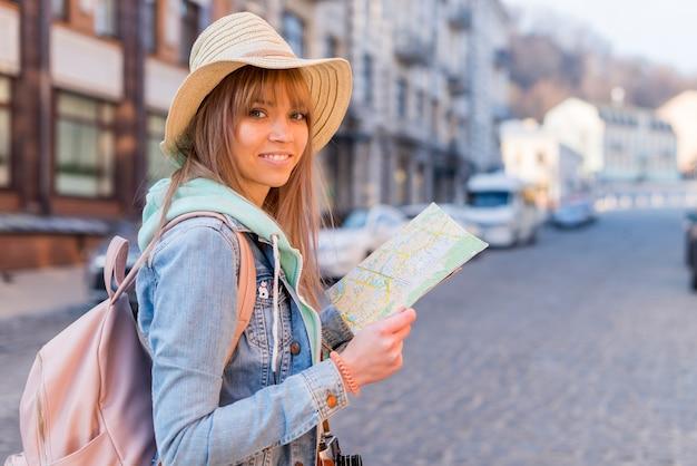 Mädchen mit dem modischen blick, der in der hand die standortkarte betrachtet kamera hält