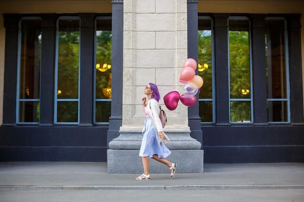 Mädchen mit dem purpurroten haar gehend im freien mit bündel helium baloons