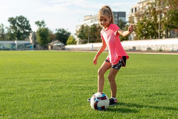 Mädchen mit dem rosa t-shirt, das fußball spielt