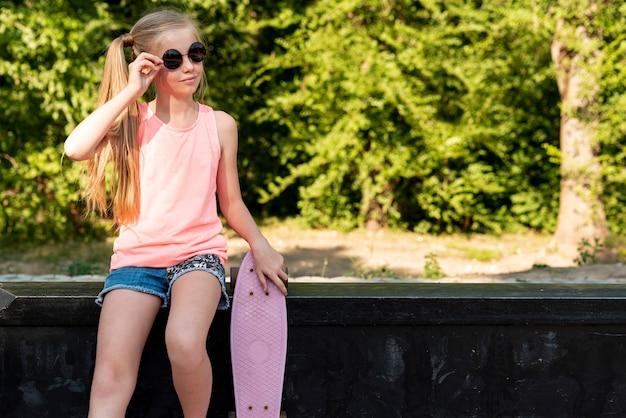 Mädchen mit dem skateboard, das auf bank sitzt