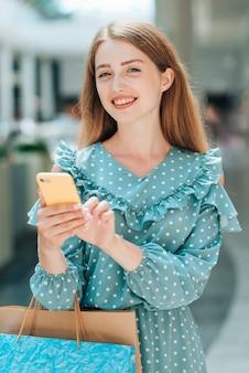 Mädchen mit dem telefon, das im mall aufwirft