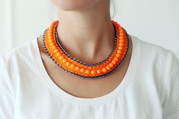 Mädchen mit dem tragen der orange halskette